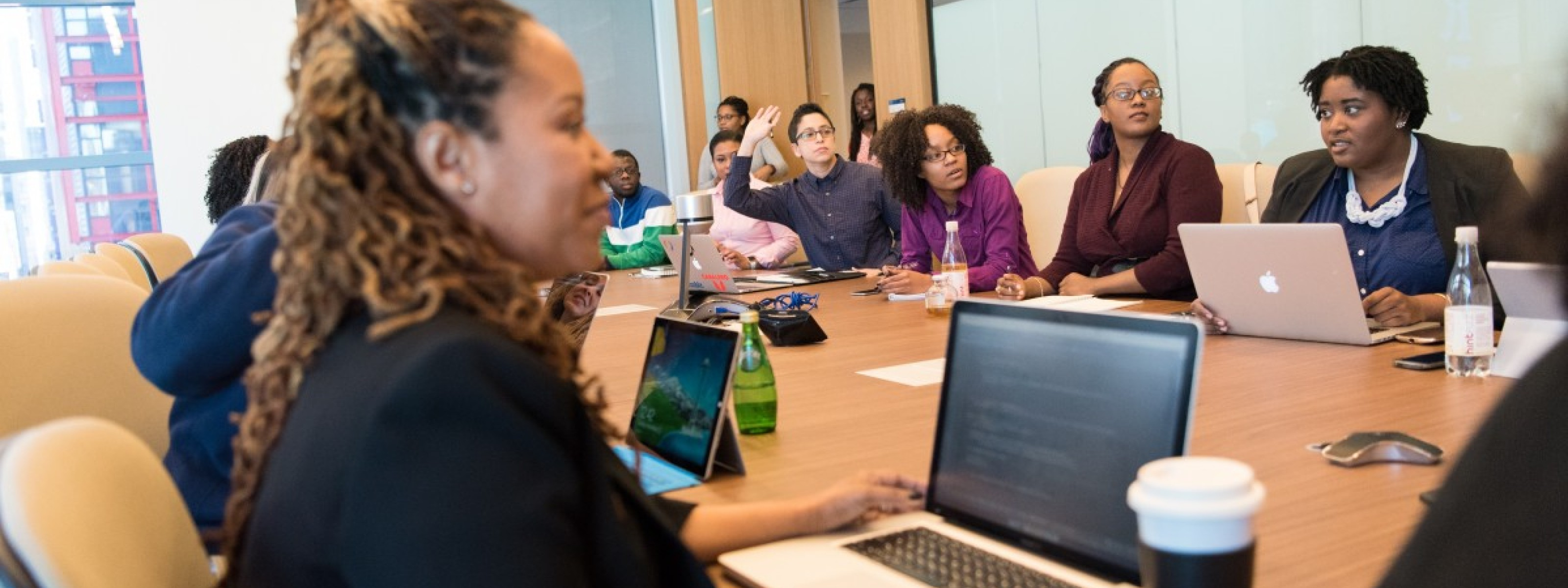 Photo of diverse group around a conference table.
